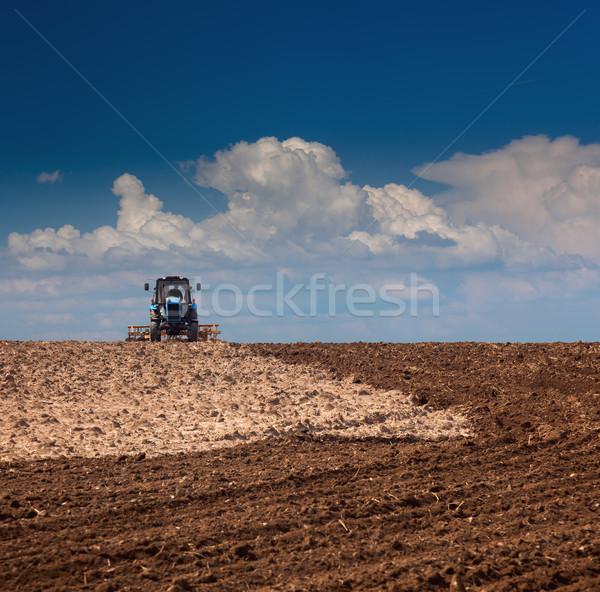 Rolniczy ciągnika pracy dziedzinie niebo Zdjęcia stock © Taiga