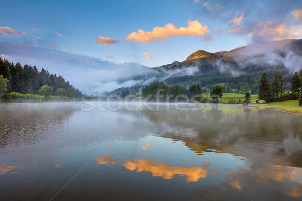 Foggy Sunrise on lake, with beautiful clouds and reflection Stock photo © Taiga