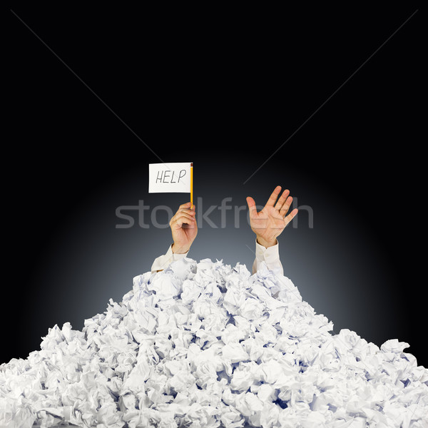Person under crumpled pile of papers with hand holding a help si Stock photo © Taiga
