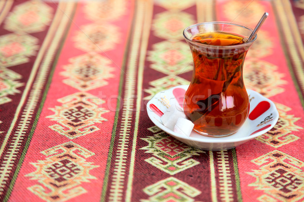 Turkish tea in traditional glass cup on handmade arabic tableclo Stock photo © Taiga