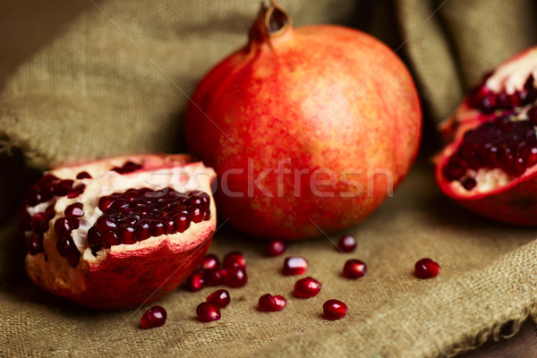Raw red pomegranate with seeds on sacking Stock photo © Taiga