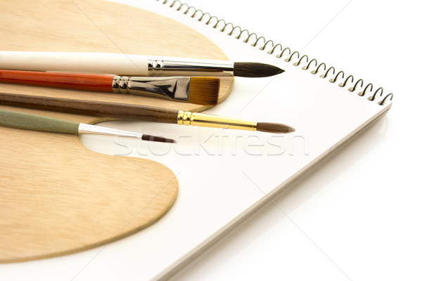Brushes with wooden palette and sketchbook isolated Stock photo © Taiga