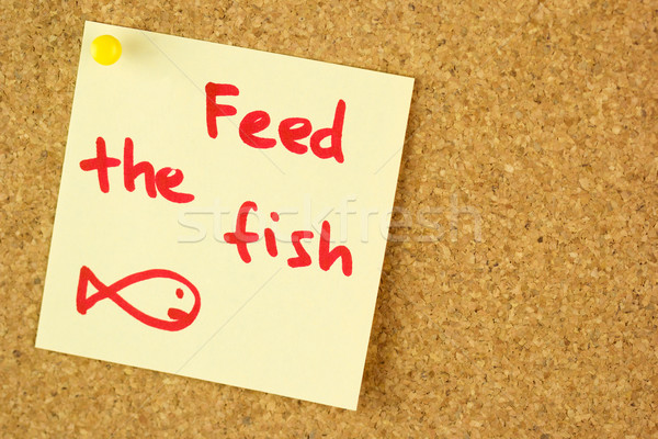 Feed the fish remind sticker on cork Stock photo © Taiga