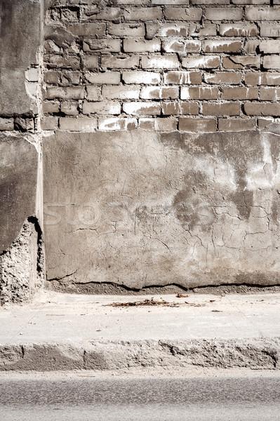 Edad agrietado yeso pared de ladrillo gris abandonado Foto stock © Taigi