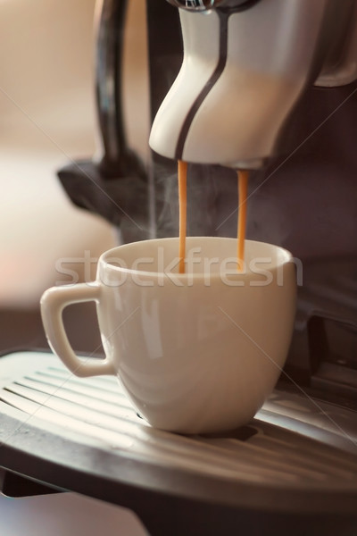 Stock photo: White cup standing on the grating of coffee machine with coffee