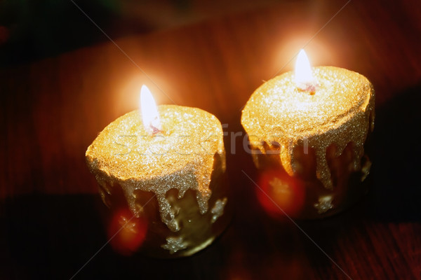 Stock photo: Close up of two lit gold candles on black background.