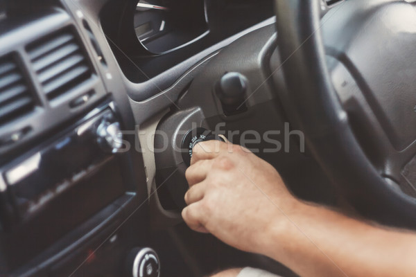 man's hand starts a car with the key in retro toning Stock photo © TanaCh