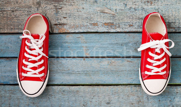 Red retro sneakers on a blue wooden background Stock photo © TanaCh