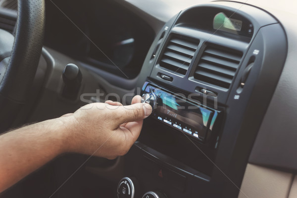 Stock photo: man's hand twists the volume in a retro toning car