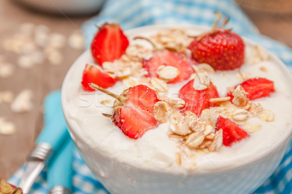 In a cup of yogurt, oat granola and fresh strawberries, on a blu Stock photo © TanaCh