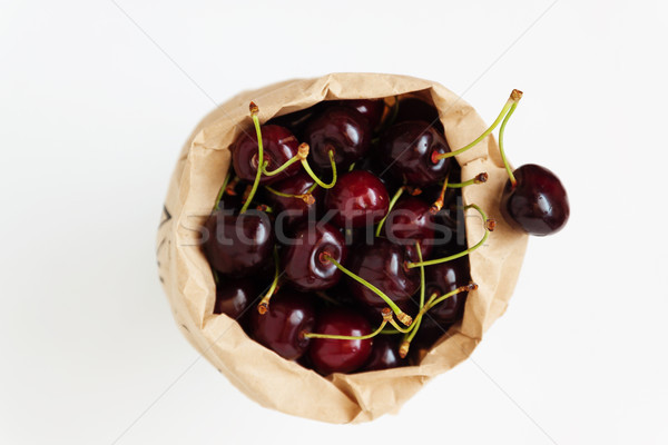 Fresh cherry berries in a paper bag, isolated on a white backgro Stock photo © TanaCh