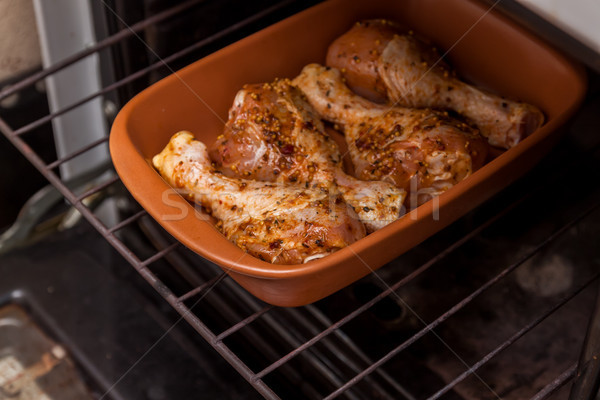 Stock photo: marinated raw chicken legs are in the oven, retro toning