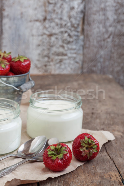 yoghurt in a glass and a bucket with fresh strawberries on a woo Stock photo © TanaCh