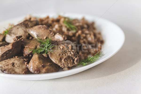 stewed chicken liver and buckwheat porridge on a white tableclot Stock photo © TanaCh