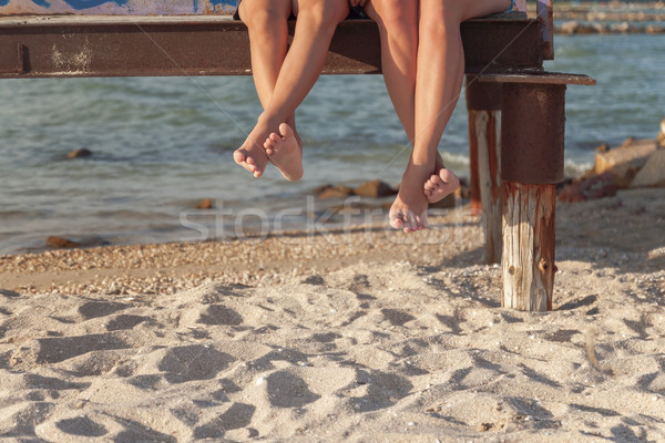 two pairs of legs dangling over the beach sand Stock photo © TanaCh