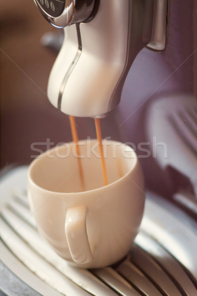 White cup standing on the grating of coffee machine with coffee  Stock photo © TanaCh