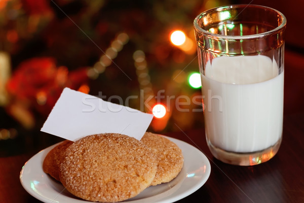 Stock photo: Christmas cookies and milk with note for Santa in front of light