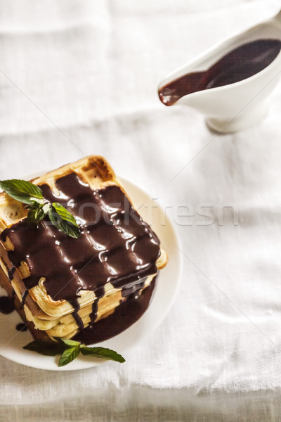 Belgian waffles and chocolate sauce in a gravy boat on a white t Stock photo © TanaCh