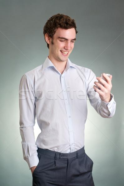 笑みを浮かべて 男 良いニュース 携帯電話 手 読む ストックフォト © tangducminh