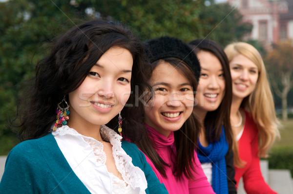 Multicultural femenino estudiantes universidad aire libre línea Foto stock © tangducminh
