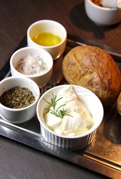 Stock photo: Baked potato on the wooden tray and mix of spices