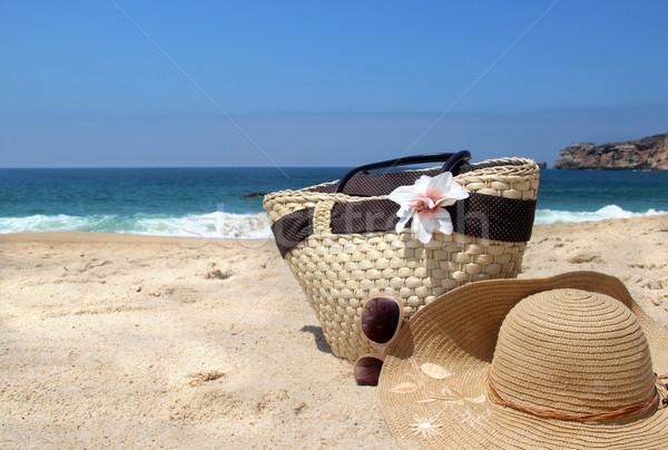 Seacoast, straw beach bag, hat and sunglasses  Stock photo © tannjuska