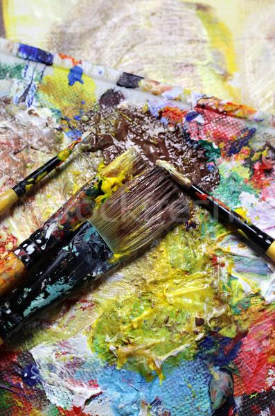 Beautiful vivid art palette and mix of paintbrushes  Stock photo © tannjuska