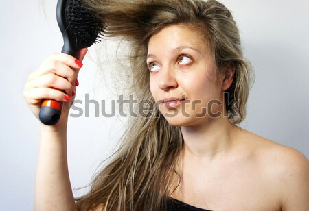 Young woman combing her hair Stock photo © tannjuska