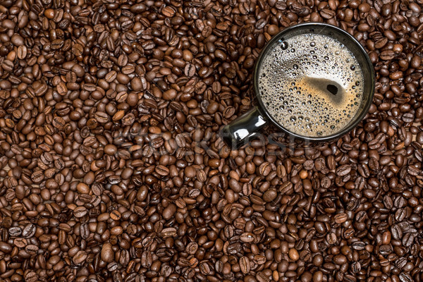 coffee beans background and black cup with hot drink Stock photo © tarczas