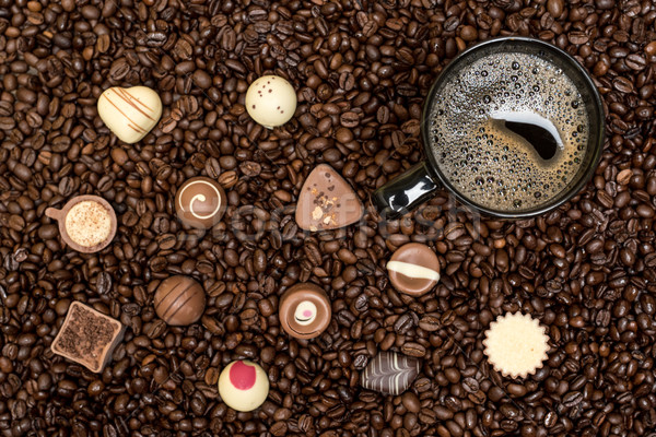 coffee beans background and black cup with pralines Stock photo © tarczas