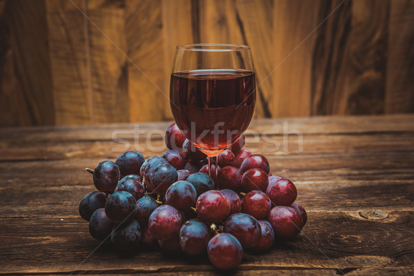 glass of wine or grape juice and fruit on wooden table Stock photo © tarczas