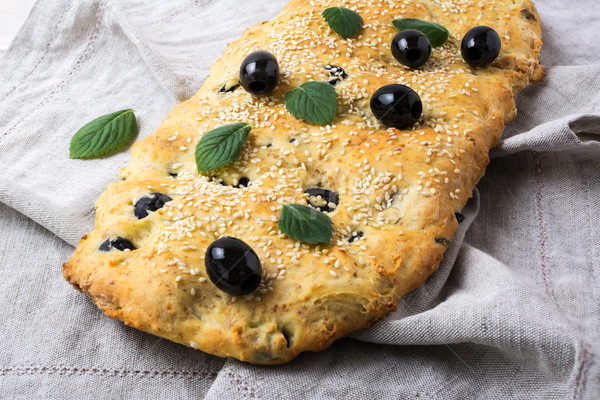 Italian bread focaccia with olive, garlic and herbs on the linen Stock photo © TasiPas