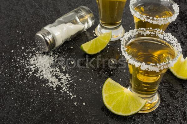 Arany tequila lövés citrus fekete közelkép Stock fotó © TasiPas