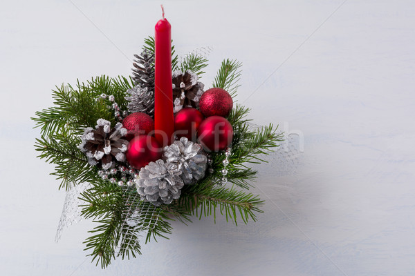 Christmas table centerpiece with red candle and silver pine cone Stock photo © TasiPas