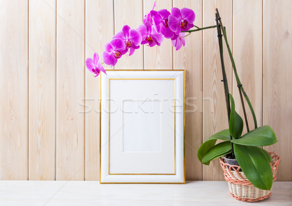 Gold decorated frame mockup with purple orchid in wicker basket  Stock photo © TasiPas