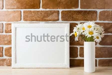 White frame mockup with daisy bouquet near exposed brick wall Stock photo © TasiPas