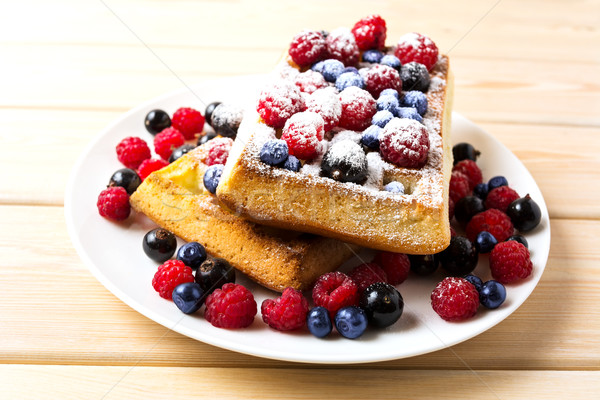 Belgian waffles with blueberry and raspberry powdered by caster  Stock photo © TasiPas