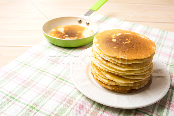 Stack of breakfast pancakes on the white plate and green pan Stock photo © TasiPas
