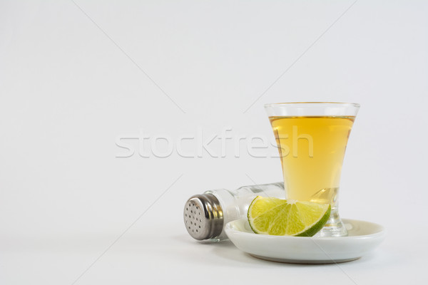 Tequila shot with lime and salt on white background Stock photo © TasiPas
