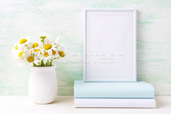 Stock photo: White frame mockup with chamomile bouquet in rustic vase and boo