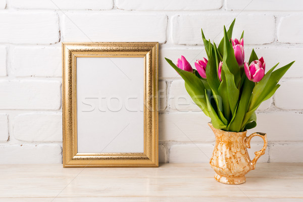 Golden frame mockup with magenta pink tulips in golden vase Stock photo © TasiPas