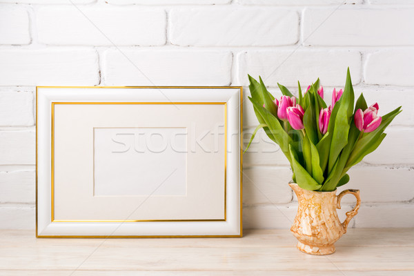 Gold decorated landscape frame mockup with bright pink tulips in Stock photo © TasiPas