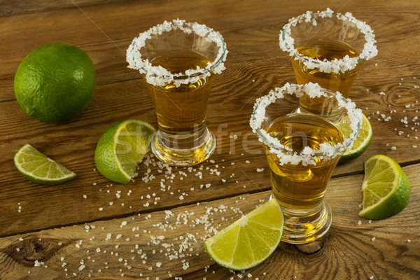 Gold tequila shots on the rustic wooden table Stock photo © TasiPas