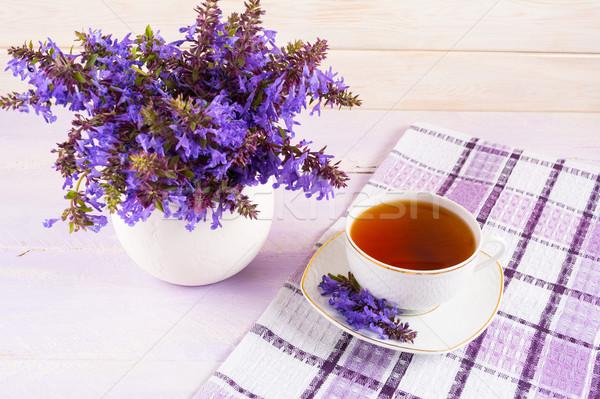 Csésze tea kockás szalvéta lila virágok Stock fotó © TasiPas