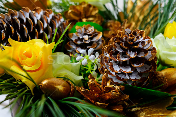 Christmas decoration with golden fir cones and silk roses Stock photo © TasiPas
