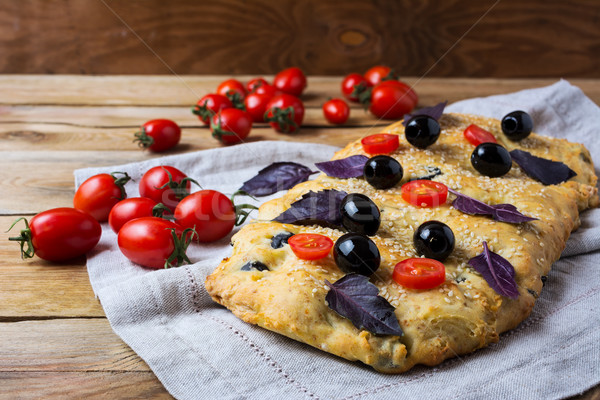 Focaccia with olive, cherry tomato and basil leaves Stock photo © TasiPas