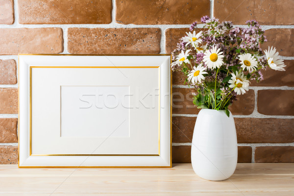 Gold decorated landscape frame mockup with wildflowers bouquet i Stock photo © TasiPas