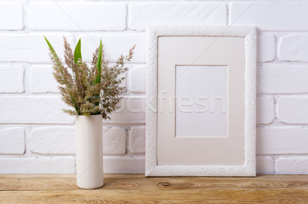 White frame mockup with grass and green leaves in cylinder vase  Stock photo © TasiPas
