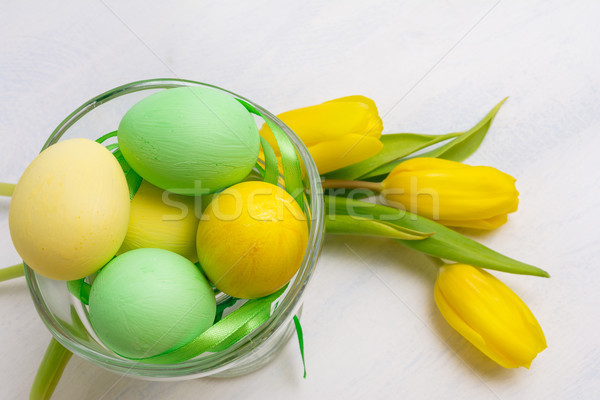 Easter table centerpiece with yellow tulips  and painted eggs in Stock photo © TasiPas