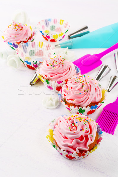 Pink birthday cupcakes  with whipped cream and cookware Stock photo © TasiPas